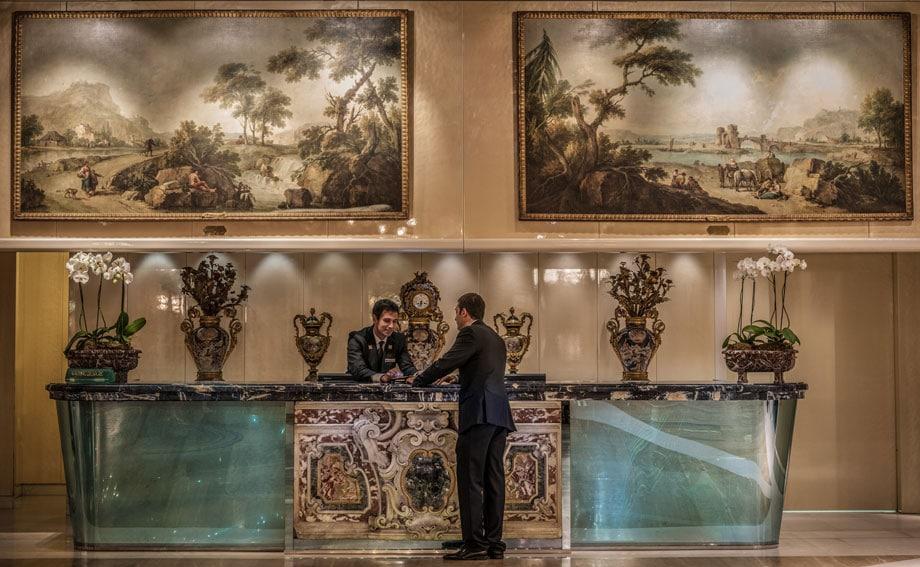 Rome Cavalieri Lobby Entrance concierge Desk with Zais Paintings - ALO Magazine